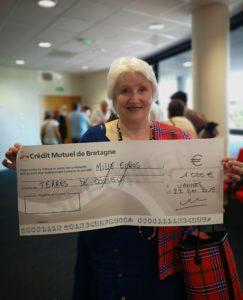 La présidente Maïtha Lobjois tenant le chèque qui aidera au programme d'Olomayiana School